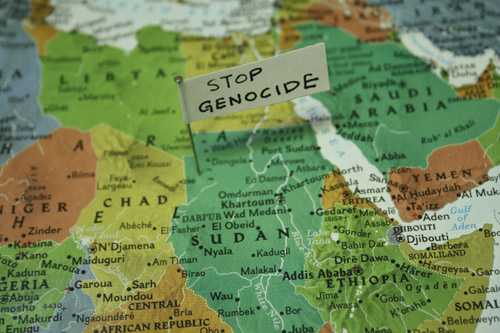 "Map close up of Africa with pin and note that says ""stop genocide""."