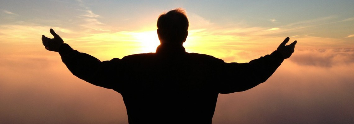 Man praying silhouetted against evening sunset